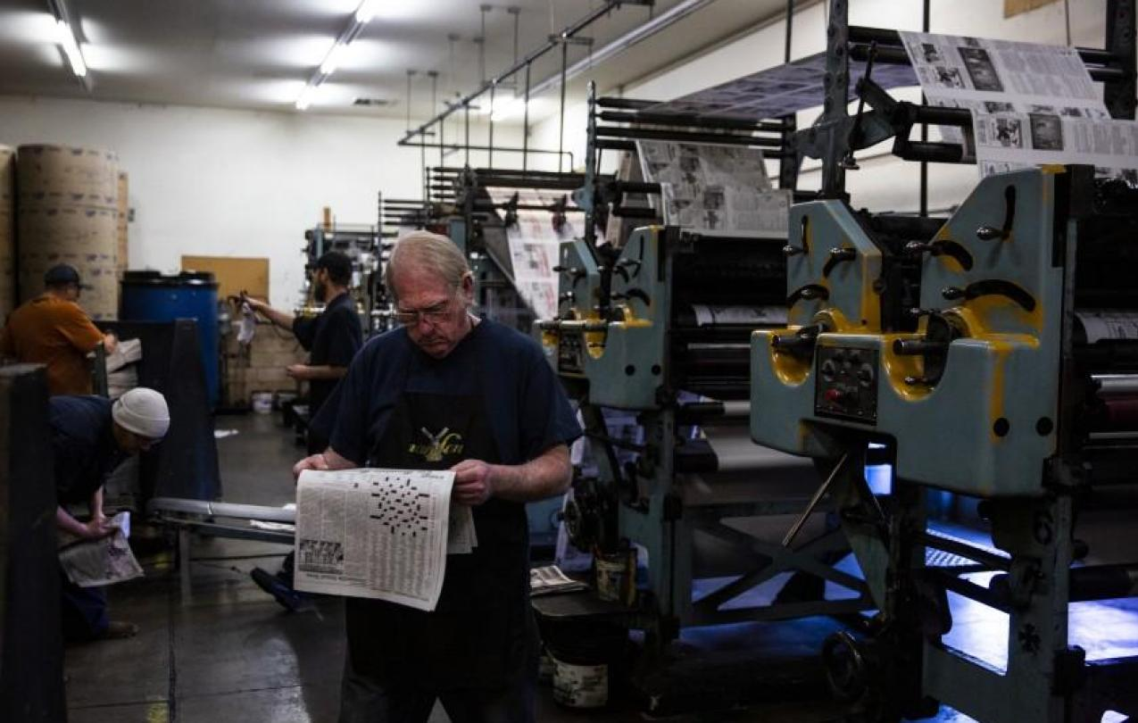 Press operators check the freshly printed issue of The Mountain Messenger, which was established in 1853 and is the oldest weekly newspaper in California.