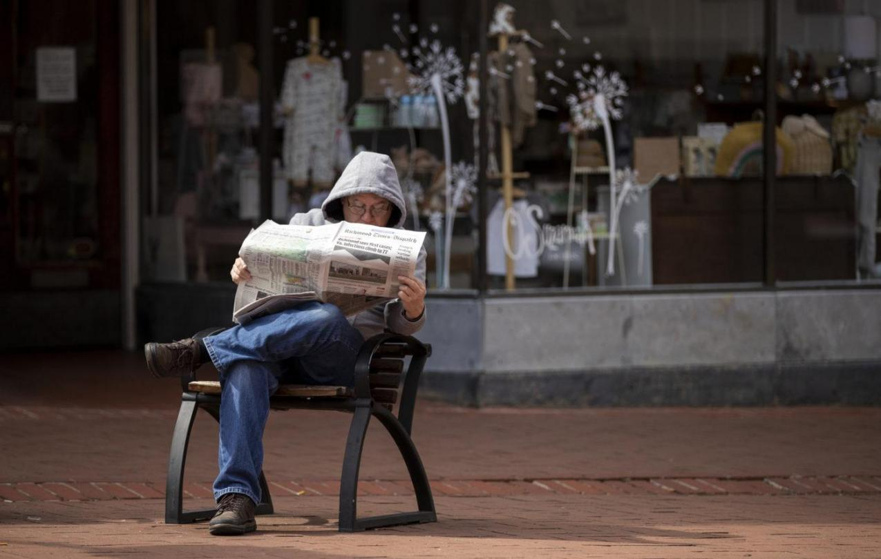 Man reading a newspaper while sitting outside.